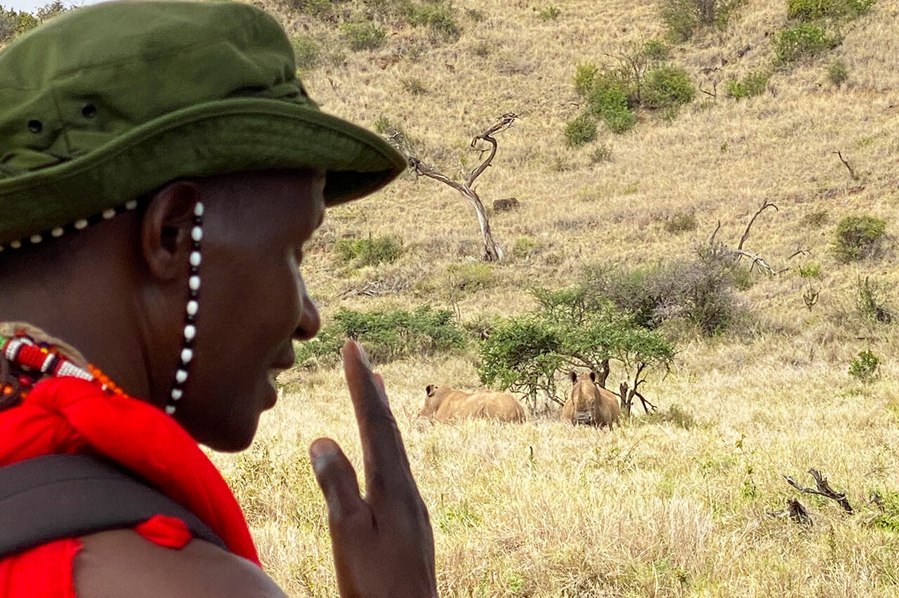 Kitonga points towards rhinos during Walking Wild nomadic safari - Photo by David Tett