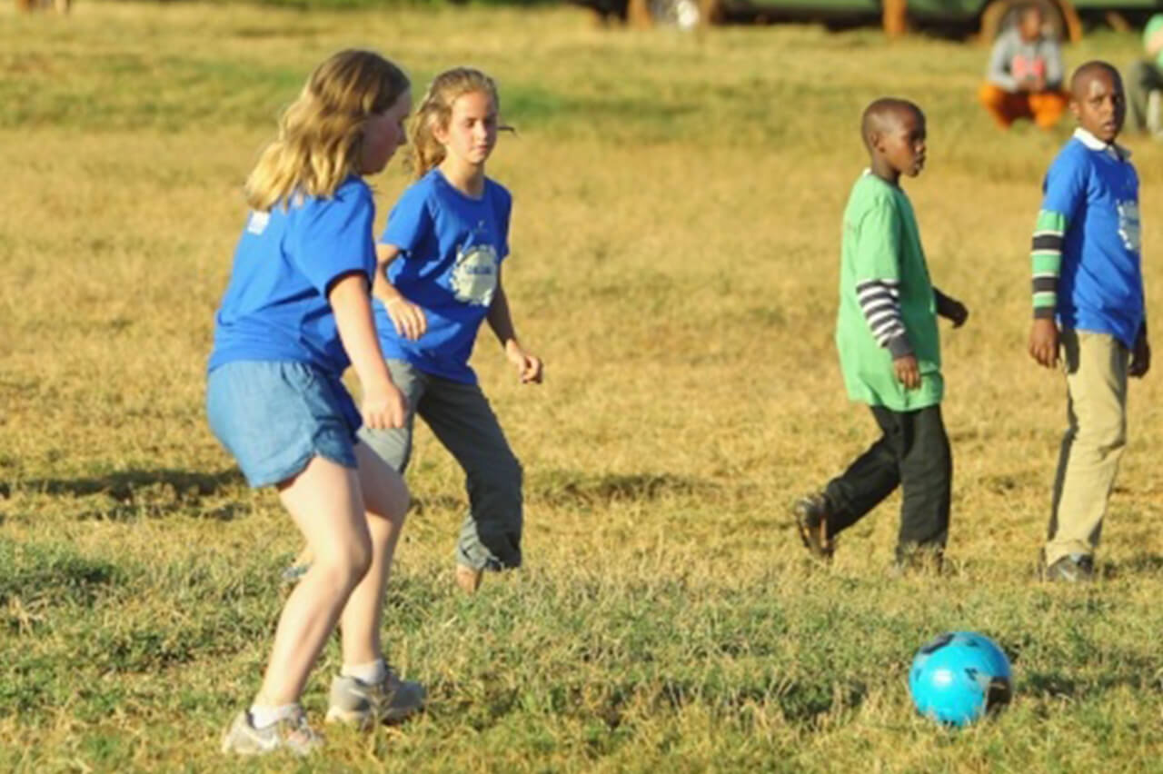 Bushtracks travelers play soccer with African locals
