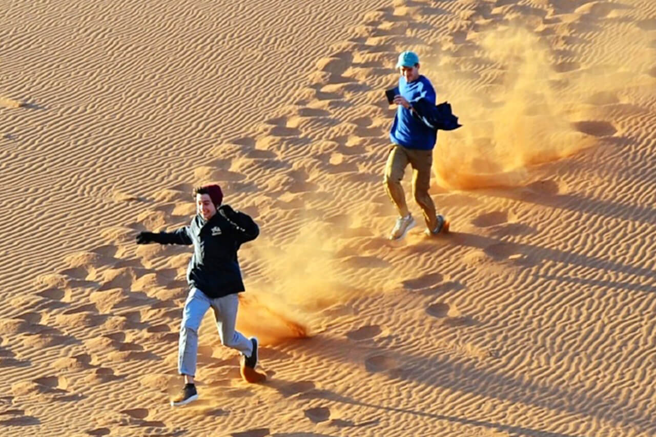 Ludwig family teens run down sand dunes in Namibia