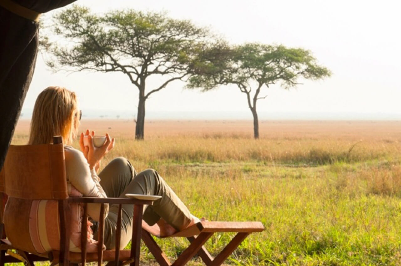 Traveler relaxes with a drink in hand at Serengeti Safari Camp