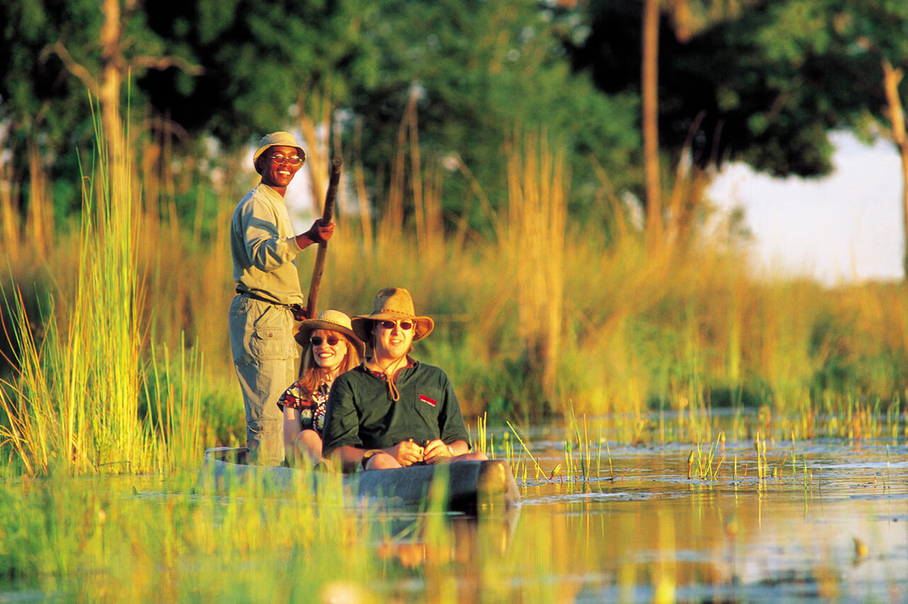 Travelers Take a Mokoro Canoe Ride in Okavango Delta in Botswana - Courtesy of Kwando