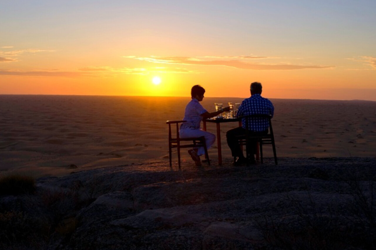 Travelers enjoy Serra Cafema cocktails in the Namib Desert