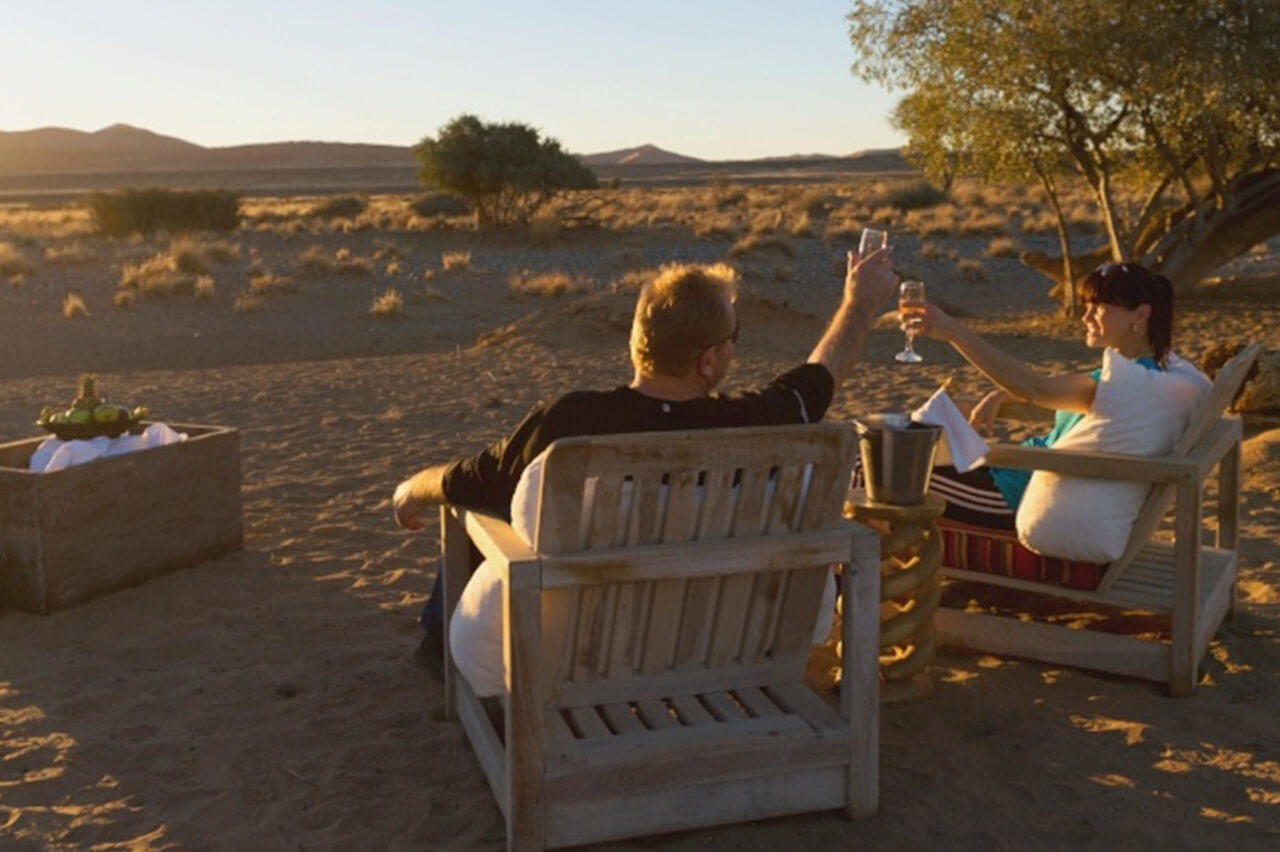 Travelers make a toast in the Namib Desert